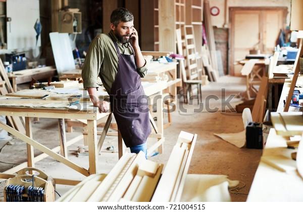 Portrait of modern bearded carpenter speaking by phone in woodworking shop taking break from work