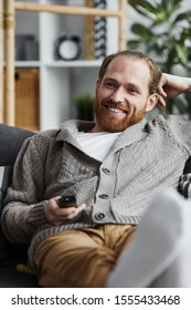 Portrait of modern bearded man smiling happily watching TV at home and holding remote control while relaxing on comfortable couch