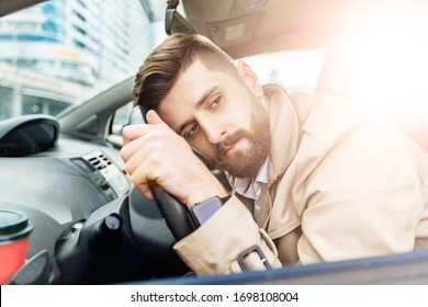 Portrait of modern bearded man at the street. Lifestyle concept with copy space. Handsome guy wear in beige jacket and white shirt. He indoors the car