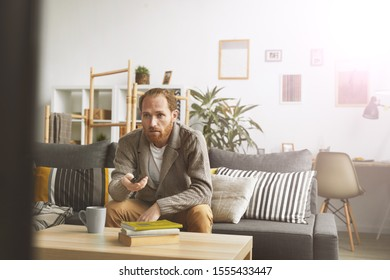 Portrait of modern bearded man watching TV at home and switching channels via remote control, copy space