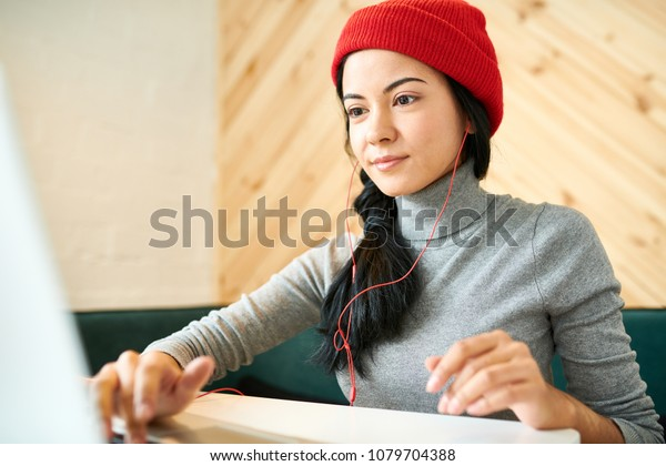 Portrait of modern beautiful woman wearing beanie hat using laptop while doing freelance work in cafe and listening to music
