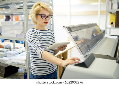 Portrait of modern blonde woman using plotter machine operating it via digital tablet while working  in printing shop, copy space