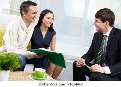 Portrait of modern couple and real estate manager discussing mortgage conditions