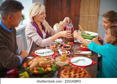 Portrait of modern family of four having festive dinner on Thanksgiving day