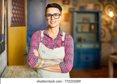 Portrait of modern female artist wearing apron and glasses looking at camera while posing confidently with arms crossed in art studio