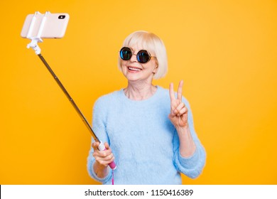 Portrait of modern grandmother holding and using selfie stick with smart phone, making selfie, gesture v-sign to the front camera isolated on vivid yellow background