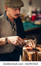 Portrait of modern handsome craftsman wearing creative cup focused on his work, taking measurements from rough leather in studio. fosus on hand