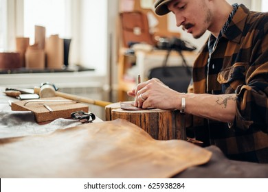 Portrait of modern handsome craftsman wearing creative cup focused on his work, taking measurements from rough leather in studio
