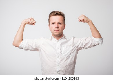 Portrait of a modern handsome man showing his power. Strong man shows muscles in his arms.