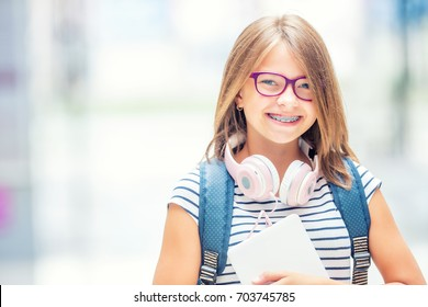 Portrait of modern happy teen school girl with backpack headphones and tablet. Girl with dental braces and glasses.