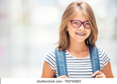 Portrait of modern happy teen school girl with backpack. Girl with dental braces and glasses.