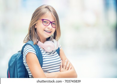 Portrait of modern happy teen school girl with backpack and headphones. Girl with dental braces and glasses.