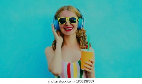 Portrait einer modernen, glücklichen jungen Frau mit Kopfhörern, die Musik auf blauem Hintergrund hört
