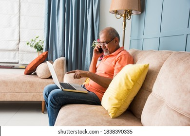 portrait of modern Indian asian senior man using laptop at while sitting on sofa and speaking on mobile or smartphone