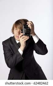 Portrait of a modern photographer using an old film camera. Studio shot. See more in my portfolio