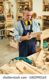 Portrait of modern senior carpenter using digital tablet while working in joinery