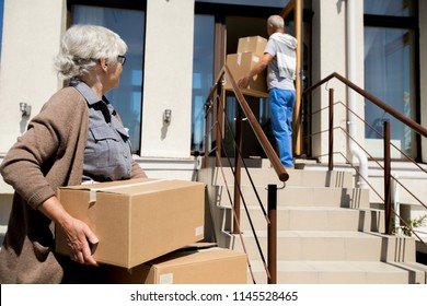 Portrait of modern senior couple unloading cardboard boxes while moving to new house, copy space