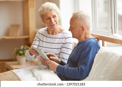 Portrait of modern senior couple using digital tablet sitting on bed in sunlight, copy space