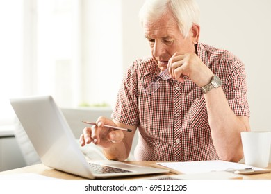 Portrait of modern senior man using laptop at home working and filling in papers