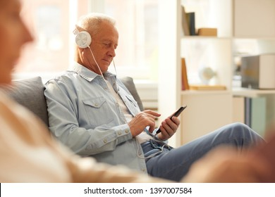 Portrait of modern senior man wearing headphones using smartphone sitting on sofa at home, copy space