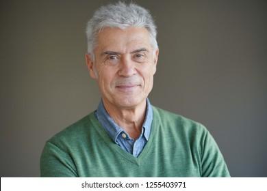 Portrait of modern smiling senior man on grey background