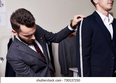Portrait of modern tailor measuring arm length of bespoke suit during model fitting in traditional atelier studio