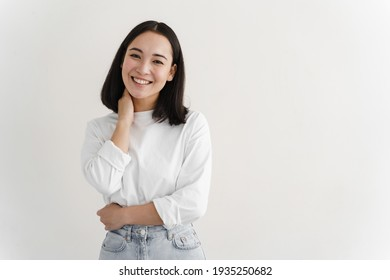 Portrait of modern woman smiling broadly at camera, standing against white background. Young girl posing in studio, copy space.