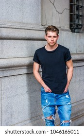 Portrait of Modern Young American Man. Young American Man with little beard, wearing black T shirt, destroyed jeans, standing by vintage wall on street in New York, looking at you.