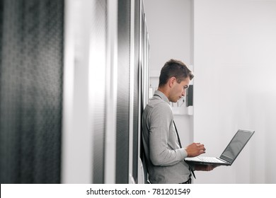 Portrait of modern young man holding laptop standing in server room working with supercomputer