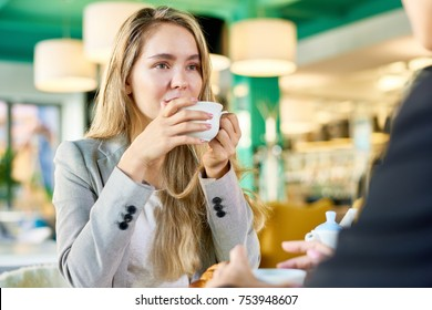 Portrait of modern young woman drinking coffee  at cafe table listening to someone sitting across from her