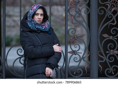 Portrait of a modern young woman, who is standing on the background of a vintage wrought-iron gate in the courtyard of an old building. Winter day in the city.