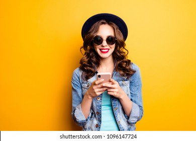 Portrait of moderngirl having smart phone in hands using wi-fi 4G internet wearing jeans jacket checking email chatting with friends searching contact isolated on yellow background
