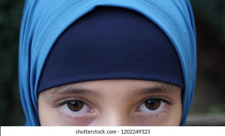 portrait of a modest girl, a Muslim wearing a hijab looks at the camera. copy space