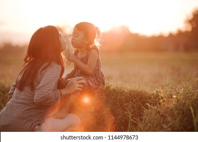 portrait of mom and daughter in beautiful sunset scenery outdoor