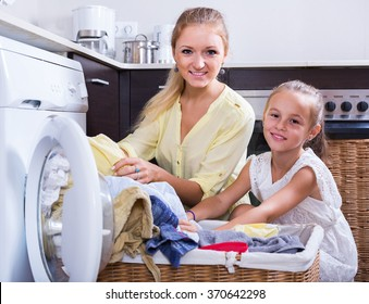 Portrait of mom and daughter with bin near washing machine