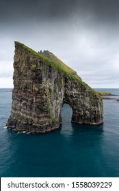 A portrait, moody sky view of Drangarnir sea stack in the Faroe Islands, topped with green grass and blue surrounding ocean water. Taken September 2019.