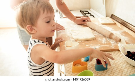 Portrait of mother with 3 years toddler son baking cookies on kitchen at morning. Happy family baking and cooking at home