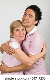 Portrait of mother and adult  son hugging and smiling together and wearing pink t shirts,they are really family,over gray background