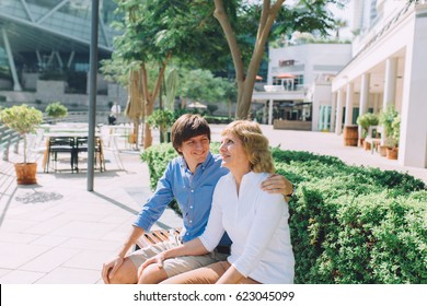 Portrait of mother and an adult son sitting outside in the park