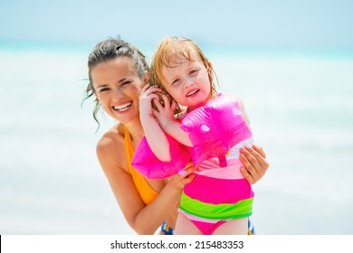 Portrait of mother and baby girl listening sound of sea in shell on sea coast