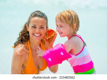 Portrait of mother and baby girl listening sound of sea in shell