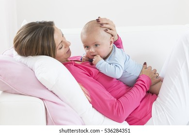 Portrait of mother and baby playing smiling at home.