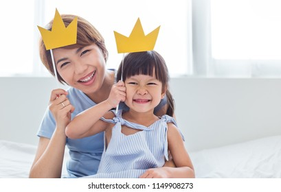 Portrait of mother and child daughter playing having fun together. Beautiful funny girl and mommy have crowns on sticks. Fun love family lifestyle single mom love mother's day holiday concept