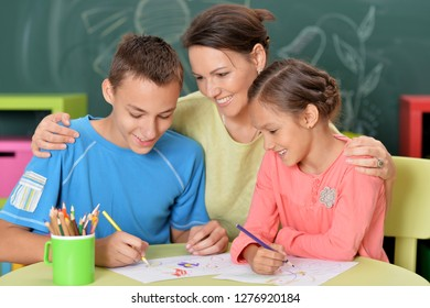 Portrait of mother with children drawing together