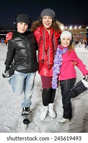 Portrait of a mother with children on skates in the winter evening