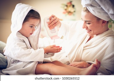 Portrait of mother and daughter after bath applying body lotion.