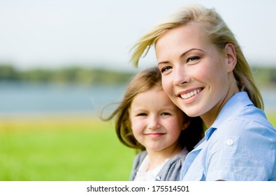 Portrait of mother and daughter against the nature view. Leisure time of happy family