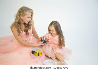 Portrait of mother and daughter in beautiful dresses with a box with live tropical butterflies