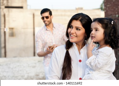portrait of mother and daughter with the father in background