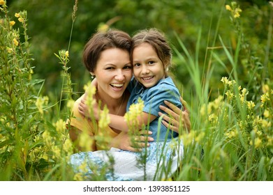 Portrait of mother and daughter at field